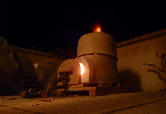 Four à bois en terre crue en train de cuire des céramiques