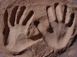Empreintes de mains dans de l'argile en poudre fine