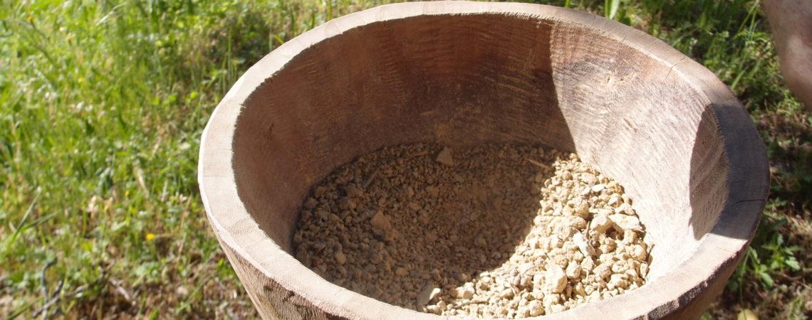 Argile sèche dans un mortier, pulvérisée au pilon
