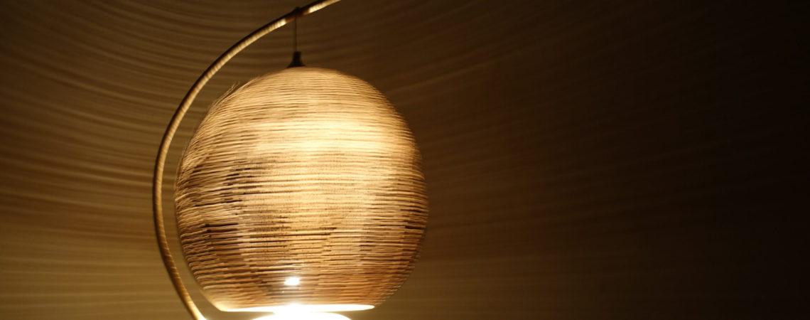 Lampe en calebasse suspendue sur pied en terre crue en rotation