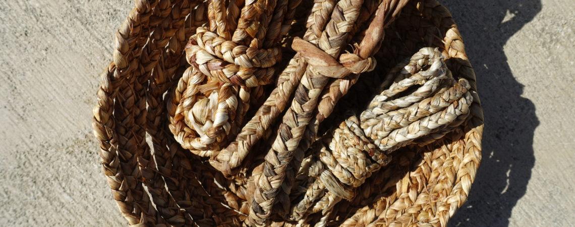 Corbeille en vannerie cordée en feuilles de yucca contenant des tresses à 3 brins